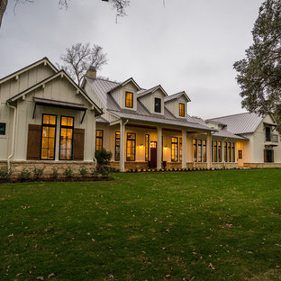 Inspiration for a large farmhouse white two-story concrete fiberboard house exterior remodel in Houston with a hip roof and a metal roof