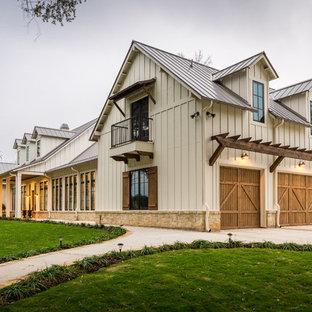 Diseño de fachada de casa beige, de estilo de casa de campo, grande, de dos plantas, con tejado a dos aguas, tejado de metal y revestimiento de aglomerado de cemento