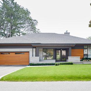 Immagine della facciata di una casa unifamiliare multicolore contemporanea a un piano di medie dimensioni con rivestimenti misti, tetto a padiglione e copertura a scandole