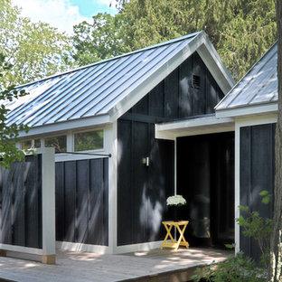 Imagen de fachada de casa azul, minimalista, de tamaño medio, de una planta, con revestimiento de madera, tejado a dos aguas y tejado de metal