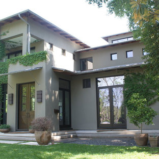 Mid-sized minimalist green two-story stucco flat roof photo in Houston