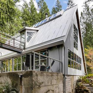 Ejemplo de fachada gris, urbana, pequeña, de dos plantas, con revestimiento de metal y tejado a dos aguas
