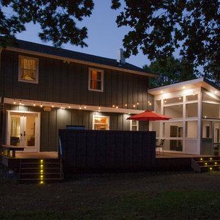 Ejemplo de fachada de casa verde, vintage, de tamaño medio, de dos plantas, con revestimiento de aglomerado de cemento, tejado a dos aguas y tejado de teja de madera