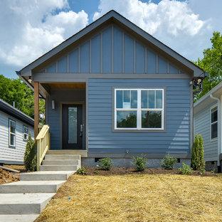 Cette photo montre une petit façade de maison bleue moderne de plain-pied avec un revêtement en panneau de béton fibré.