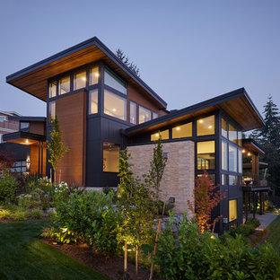 Modern inredning av ett mycket stort svart hus, med tre eller fler plan, blandad fasad och platt tak