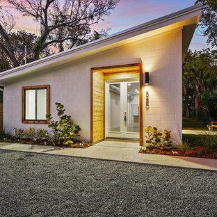 Modern inredning av ett mellanstort vitt hus, med allt i ett plan, pulpettak och tak i metall