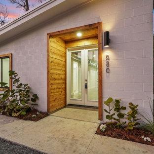 Cette photo montre une façade de maison blanche moderne de taille moyenne, de plain-pied et en briques peintes avec un toit en appentis et un toit en métal.