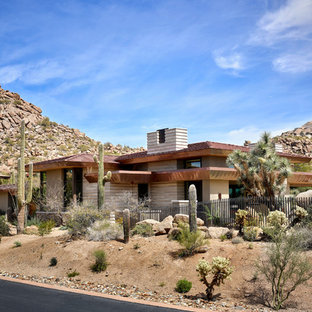 Southwestern beige two-story house exterior idea in Phoenix with a hip roof