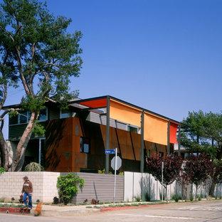 Idée de décoration pour une façade métallique orange urbaine à un étage.