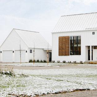 Inspiration för ett mellanstort lantligt vitt hus, med två våningar och pulpettak