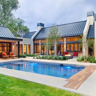 Immagine della facciata di una casa unifamiliare beige country a due piani di medie dimensioni con rivestimenti misti, tetto piano e copertura in metallo o lamiera