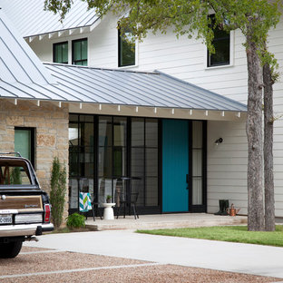 Example of a country two-story mixed siding exterior home design in Austin with a metal roof