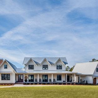 Foto de fachada de casa blanca, de estilo de casa de campo, de dos plantas, con tejado a dos aguas y tejado de metal