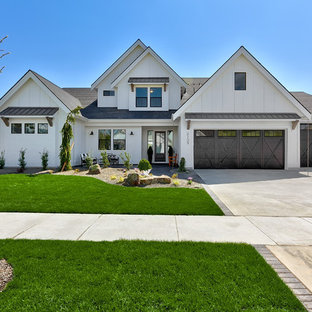 Large farmhouse white two-story wood exterior home photo in Boise