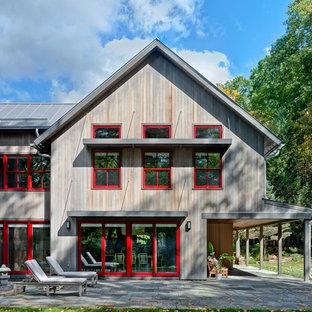 Modelo de fachada de casa gris, de estilo de casa de campo, grande, de dos plantas, con revestimiento de madera, tejado a dos aguas y tejado de metal