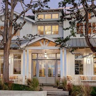 Aménagement d'une grand façade de maison blanche campagne à un étage avec un revêtement en vinyle et un toit à deux pans.