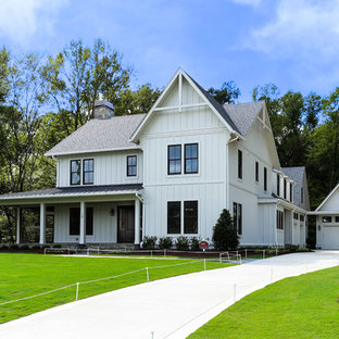 Large cottage white two-story wood and board and batten gable roof idea in Raleigh