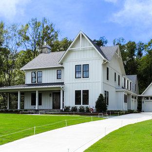Esempio della facciata di una casa grande bianca in campagna a due piani con rivestimento in legno e tetto a capanna