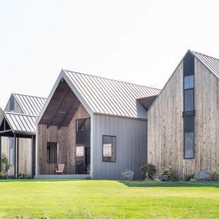 Diseño de fachada de casa marrón, actual, grande, de tres plantas, con revestimiento de madera, tejado a dos aguas y tejado de metal