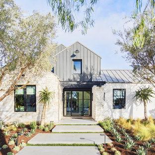 Foto på ett stort lantligt flerfärgat hus, med två våningar, blandad fasad, sadeltak och tak i metall