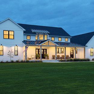 Стильный дизайн: большой, двухэтажный, белый частный загородный дом в стиле модернизм с облицовкой из винила, плоской крышей и металлической крышей - последний тренд