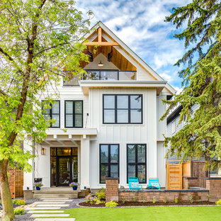 Example Of A Large Country White Two Story Gable Roof Design In Calgary