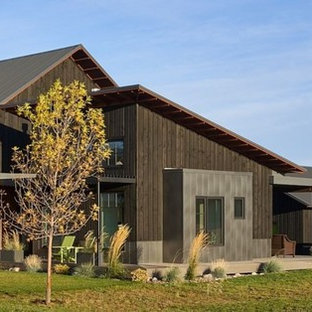 Cottage black two-story wood house exterior idea in Boise with a metal roof