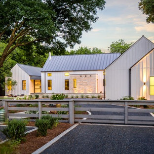 Foto della facciata di una casa grande bianca country a due piani con rivestimento in legno e tetto a capanna