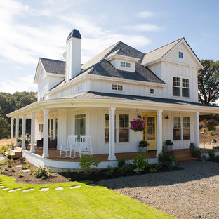 Example of a mid-sized country white two-story exterior home design in Portland with a hip roof and a shingle roof