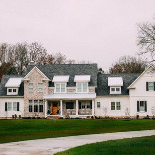 Foto della facciata di una casa unifamiliare grande bianca country a due piani con rivestimenti misti, tetto a capanna e copertura mista