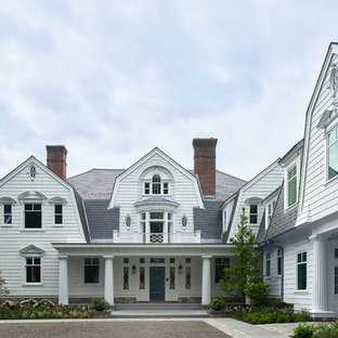 Inspiration for a cottage white two-story house exterior remodel in New York with a gambrel roof and a shingle roof