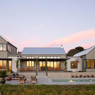 Cette photo montre une façade de maison grise nature à un étage.
