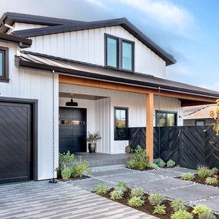 Réalisation d'une grand façade de maison blanche champêtre à un étage avec un revêtement en panneau de béton fibré et un toit à deux pans.