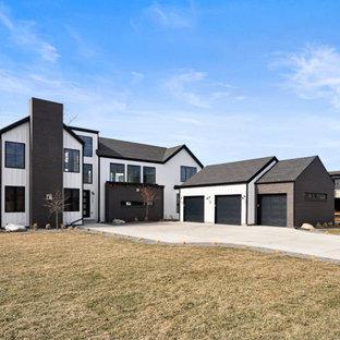 Неиссякаемый источник вдохновения для домашнего уюта: двухэтажный, кирпичный, белый частный загородный дом в стиле модернизм с двускатной крышей, крышей из гибкой черепицы, черной крышей и отделкой доской с нащельником