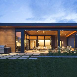 Ispirazione per la facciata di una casa unifamiliare nera moderna a un piano di medie dimensioni con rivestimenti misti, tetto piano e copertura in metallo o lamiera