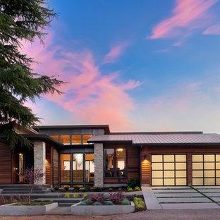 Diseño de fachada de casa marrón, actual, de tamaño medio, de dos plantas, con revestimiento de madera, tejado de un solo tendido y tejado de metal