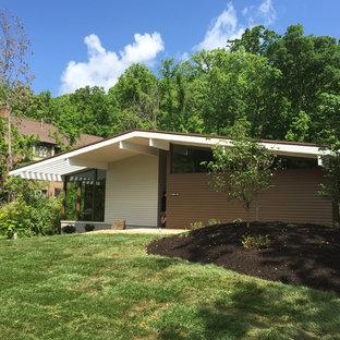 Idée de décoration pour une façade de maison beige vintage de taille moyenne et de plain-pied avec un revêtement en panneau de béton fibré et un toit en appentis.