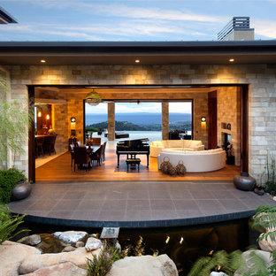 Inspiration pour une grand façade de maison marron ethnique à un étage avec un revêtement en stuc.