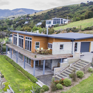 Идея дизайна: двухэтажный, разноцветный частный загородный дом в морском стиле с комбинированной облицовкой, крышей-бабочкой и металлической крышей