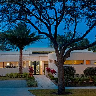 Idéer för mellanstora funkis vita hus, med allt i ett plan, platt tak och stuckatur
