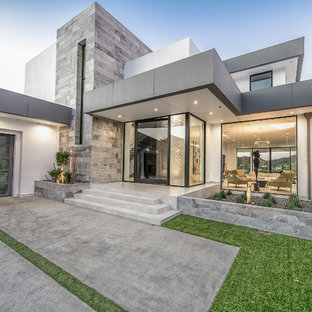 Example of a huge trendy white two-story stucco exterior home design in Los Angeles