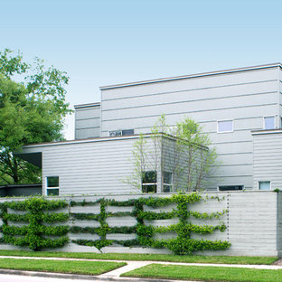 Design ideas for a mid-sized modern two-storey grey exterior in Houston with concrete fiberboard siding and a flat roof.