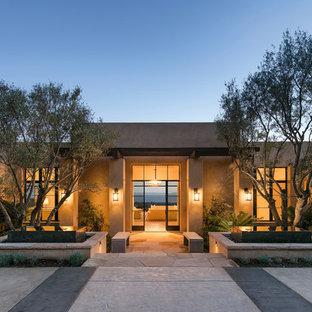 Идея дизайна: одноэтажный, большой фасад дома бежевого цвета в стиле фьюжн с плоской крышей и облицовкой из самана