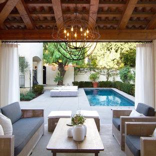 Modelo de fachada de casa beige, tradicional renovada, grande, de dos plantas, con revestimiento de estuco y tejado de teja de barro
