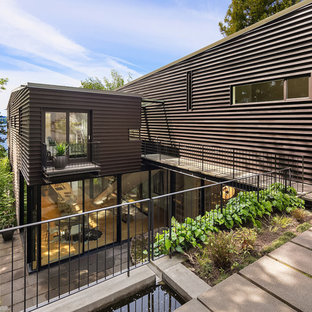 Beach style brown two-story metal house exterior idea in Seattle with a shed roof