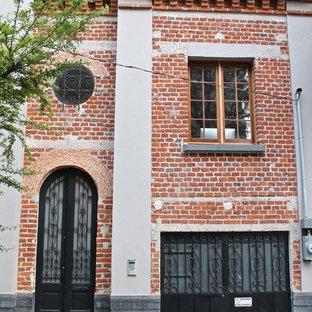 Imagen de fachada de casa pareada roja, bohemia, de dos plantas, con revestimiento de ladrillo y tejado plano