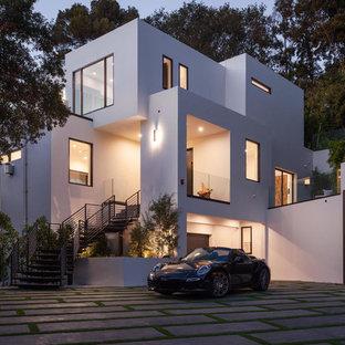 Réalisation d'une très grand façade de maison blanche minimaliste à deux étages et plus avec un revêtement en stuc et un toit plat.