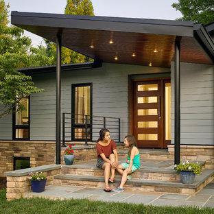 Пример оригинального дизайна: одноэтажный, синий дом среднего размера в стиле ретро с облицовкой из ЦСП и вальмовой крышей