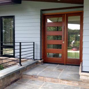 Foto de fachada gris, retro, de tamaño medio, de una planta, con revestimiento de aglomerado de cemento y tejado a cuatro aguas