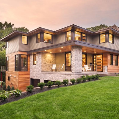 Huge minimalist gray two-story mixed siding house exterior photo in Minneapolis with a hip roof and a mixed material roof